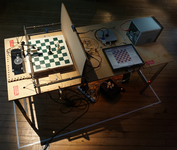 Correspondence, 2019:  installation view Motorised chess board, cctv camera, video monitor,customized circuits and software, electromagnets, python script linked to public chess forum